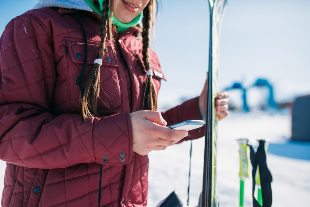 Female skier holds phone in hand.